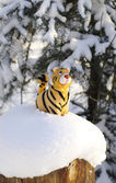 Statuette tiger on snow-bound stub — Stock Photo