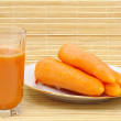 Fresh neat juice and carrot on plate - Stock Photo