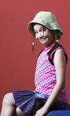 Girl with a hat sitting — Stock Photo