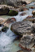 Clear brook beside black-brown stones. — Stock Photo