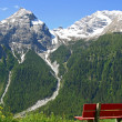 Snowy peaks and a bench to relax — Stockfoto
