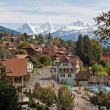 Swiss village with snowy peaks - Stock Photo