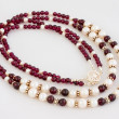 Garnet and pearl necklace over white — Stock Photo