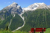 Snowy peaks and a bench to relax — Stock Photo