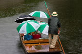 Punt with tourists under umbrellas — Stock Photo