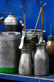 Antique oil cans in a workshop — Stock Photo