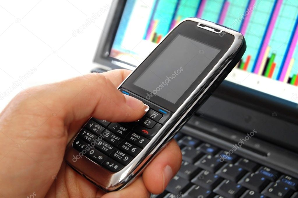 Hand holding a modern mobile phone. Laptop with bright statistic graph on screen on the background.  Stock Photo #2009240