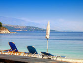 Parasol and sunbeds on the pebble beach — Stock Photo