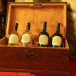 Four bottles of wine in a wooden box in - Stock Photo