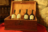 Four bottles of wine in a wooden box in — Stock Photo