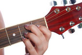 Girl hand on fingerboard guitar — Stockfoto