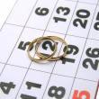 Stock Photo: Wedding rings on a calendar