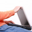Young man closing his laptop - Stock Photo