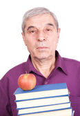 Senior professor with apple and books — Stock Photo