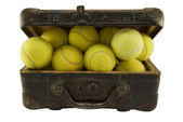 Old suitcase full of tennis balls — Stock Photo