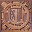 Closed manhole with emblem in Dresden - Stock Photo