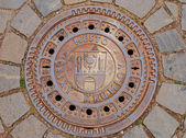Closed manhole with emblem in Cesky Krum — Stock Photo