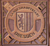 Closed manhole with emblem in Dresden — Stok fotoğraf