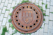 Closed manhole with emblem in Prague — Stok fotoğraf