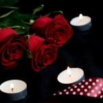 Три красных роз и зажженные свечи — Стоковое фото
