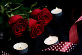 Three red Roses and burning candles — Stock Photo