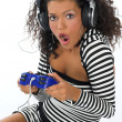 Stock Photo: Beautiful curly brunette girl playing game conso