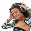 Beautiful curly brunette girl listening music — Stock Photo #1796626
