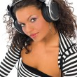 Stock Photo: Beautiful curly brunette girl listening music