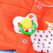 Pacifier and baby clothes, close-up — Stock Photo