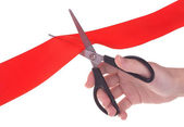 Hand with scissors cutting red ribbon — Stock Photo