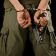 Man in handcuffs with a gun — Stockfoto