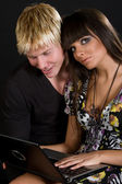 Beautiful young couple with laptop — Stock Photo