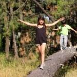 Girl walking across log — Stock Photo