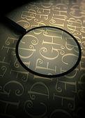 Szkło powiększające z streszczenie tekst — Zdjęcie stockowe