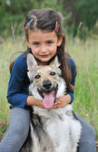 Little girl and her baby wolf dog — Stock Photo