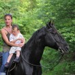 Royalty-Free Stock Photo: Mother, son and black horse