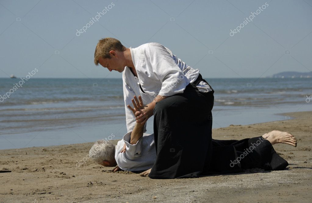 Two adults are training in Aikido on the beach  Stock Photo #1860208