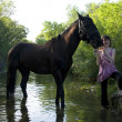 Child and horse in river - Stock Photo