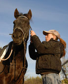 Teenager, bridle and horse — Stock Photo