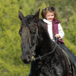 Little girl and her black horse — Stock Photo