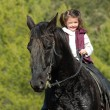 Little girl and her black horse - Stock Photo