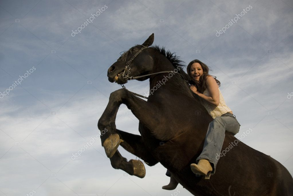 Happy girl and rearing stallion in blue sky  Stock Photo #2026660