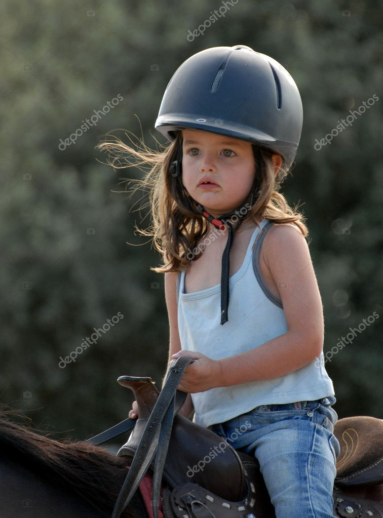Very young little girl on her black stallion — Stock Photo #2029458
