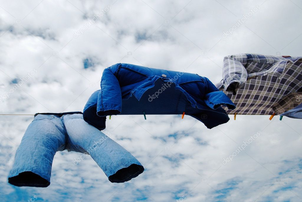 Drying trousers and shirts on wind with copy space over cloudy sky background — Stock Photo #1867409