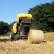 Baler discharging a haybale — Stock Photo
