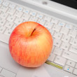 Red apple over grey laptop — Stock Photo