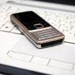 Silver mobile phone on grey laptop — Stock Photo