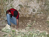 Archeologist examining floor of a troglodyte dwelling cave in Malta — Stock Photo