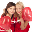 Two  girls with red heart balloon - Stockfoto