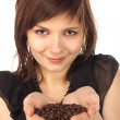 Woman holding coffee beans — Stock Photo